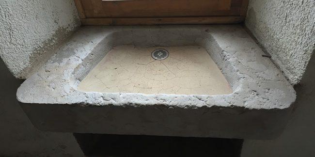 Décapage d'un évier en pierre ancien par le traité d'aérogommage